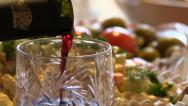 Stock Video Footage of Red wine is poured into the glass on a background of a celebratory table
