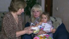 Grandmother feeding granddaughter while mom rests. Slider. Stock Footage