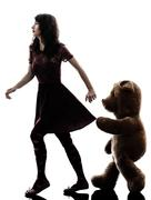 Strange young woman and vicious teddy bear  silhouette Stock Photos