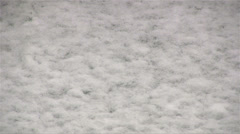 Snow falling on concrete path and sticking Stock Footage