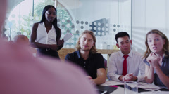 Attractive young mixed ethnicity business team in a boardroom meeting. - stock footage