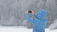 Stock Video Footage of Young woman taking photograph by cellphone in winter scenery HD