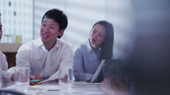 Attractive young multi ethnic business team in a boardroom meeting - stock footage