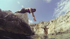 SLOW MOTION: Young woman jumping into the ocean Stock Footage
