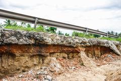 cracked concrete road - stock photo