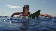 SLOW MOTION: Female surfer paddling out Stock Footage