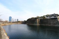 a moat surrounding osaka castle in japan, winter - stock photo