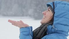 The young girl catches snowflakes, slow motion, close up  HD Stock Footage