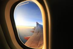 Window airplane travel time is sunset. Stock Photos