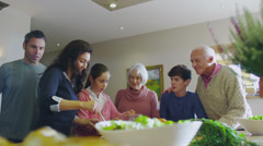 3 generations of happy family preparing a meal together in the kitchen at home - stock footage