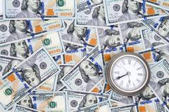 american 100 dollar bills with a vintage watch - stock photo