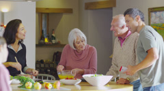 3 generations of happy family preparing a meal together in the kitchen at home Stock Footage