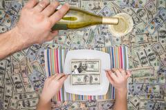 man eating dollars as a servant pours champagne - stock photo
