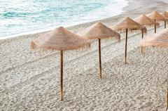straw parasols on empty beach. nerja, spain - stock photo
