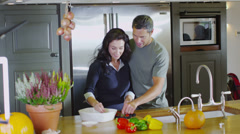 Happy affectionate couple preparing food together in the kitchen at home - stock footage