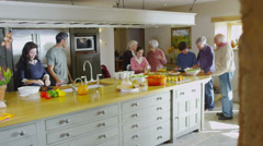 Extended group of family and friends preparing food & socializing in the kitchen - stock footage