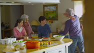 Stock Video Footage of Extended group of family and friends preparing food & socializing in the kitchen