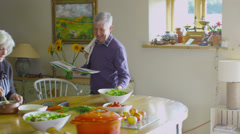 Happy mature couple following a recipe & preparing food together in the kitchen - stock footage