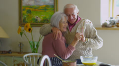Happy young at heart senior couple preparing food together in kitchen at home - stock footage
