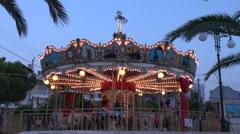 Children's carousel horse spinning around, merry-go-round, amusement park, dusk Stock Footage