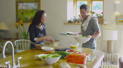 Happy couple following a recipe and preparing food together in the kitchen - stock footage