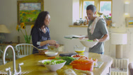 Stock Video Footage of Happy couple following a recipe and preparing food together in the kitchen