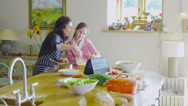 Stock Video Footage of Mother and daughter following a recipe and preparing food together at home