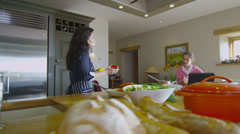 Mother and daughter following a recipe and preparing food together at home - stock footage