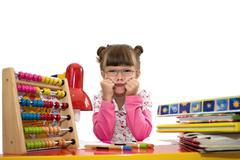 Cute little girl with glasses is drawing with felt-tip pen in preschool Stock Photos