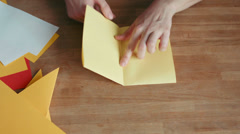 Hands making origami ship with yellow paper Stock Footage