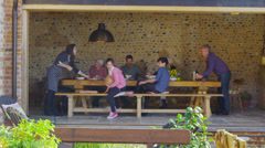 Happy extended family group enjoying a meal together in countryside home - stock footage