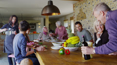 Happy extended family group sit down to enjoy a meal together at home - stock footage