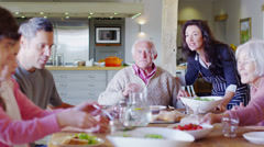 Happy affectionate family group eating lunch at home - stock footage