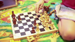 One pretty girl playing chess on wooden chessboard - stock footage