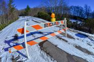 Stock Photo of road block set up before snowy and icy road