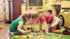 Pretty girls playing chess on the floor of nursery Stock Footage