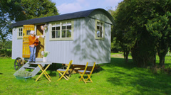 Cheerful senior couple relaxing outside quaint caravan in a natural setting - stock footage