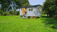 Cheerful senior couple relaxing outside quaint caravan in a natural setting Stock Footage