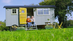 Stock Video Footage of Cheerful senior couple relaxing outside quaint caravan in a natural setting