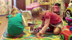 Two little girls playing chess in domestic room Stock Footage