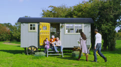 Cheerful family relaxing together outside quaint caravan in a natural setting - stock footage