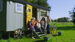 Cheerful family relaxing together outside quaint caravan in a natural setting Stock Footage