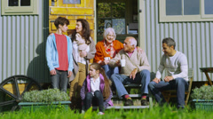 Portrait of happy extended family sitting outside caravan on an autumn day - stock footage