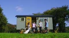 Extended family group outside quaint caravan with chickens and ducks - stock footage