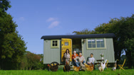 Stock Video Footage of Extended family group outside quaint caravan with chickens and ducks