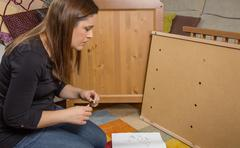 girl reading instructions to assemble furniture - stock photo