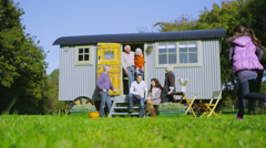 Happy extended family group relaxing outside quaint caravan in a natural setting - stock footage