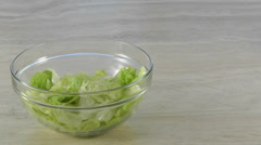Lettuce drops into salad bowl with copy space to right Stock Footage