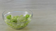 Stock Video Footage of Lettuce drops into salad bowl with copy space to right