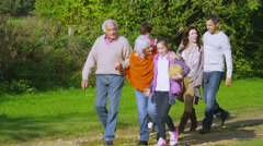 Happy extended family group walking in the countryside on an autumn day - stock footage